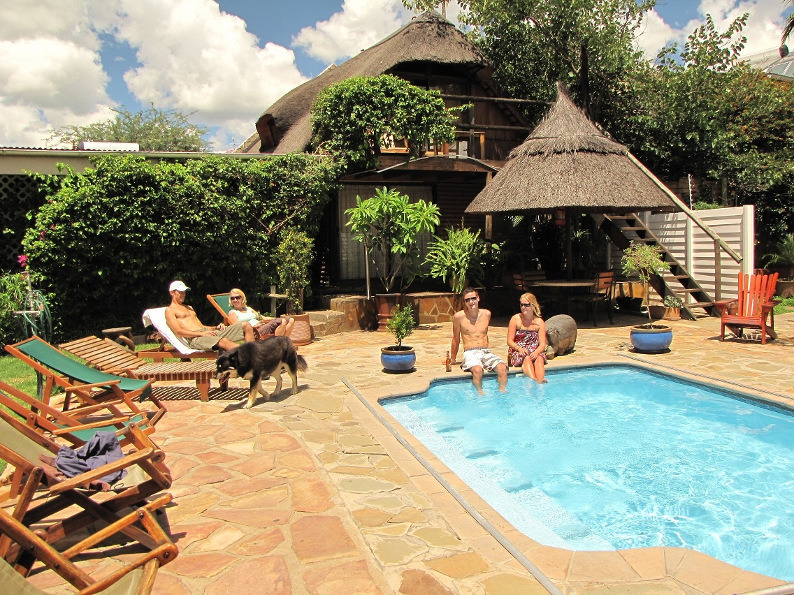 People relaxing at the pool at Chameleon Backpackers hostel