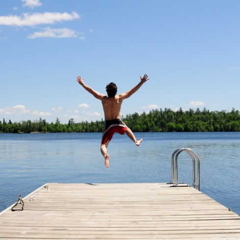 man jumping into a lake