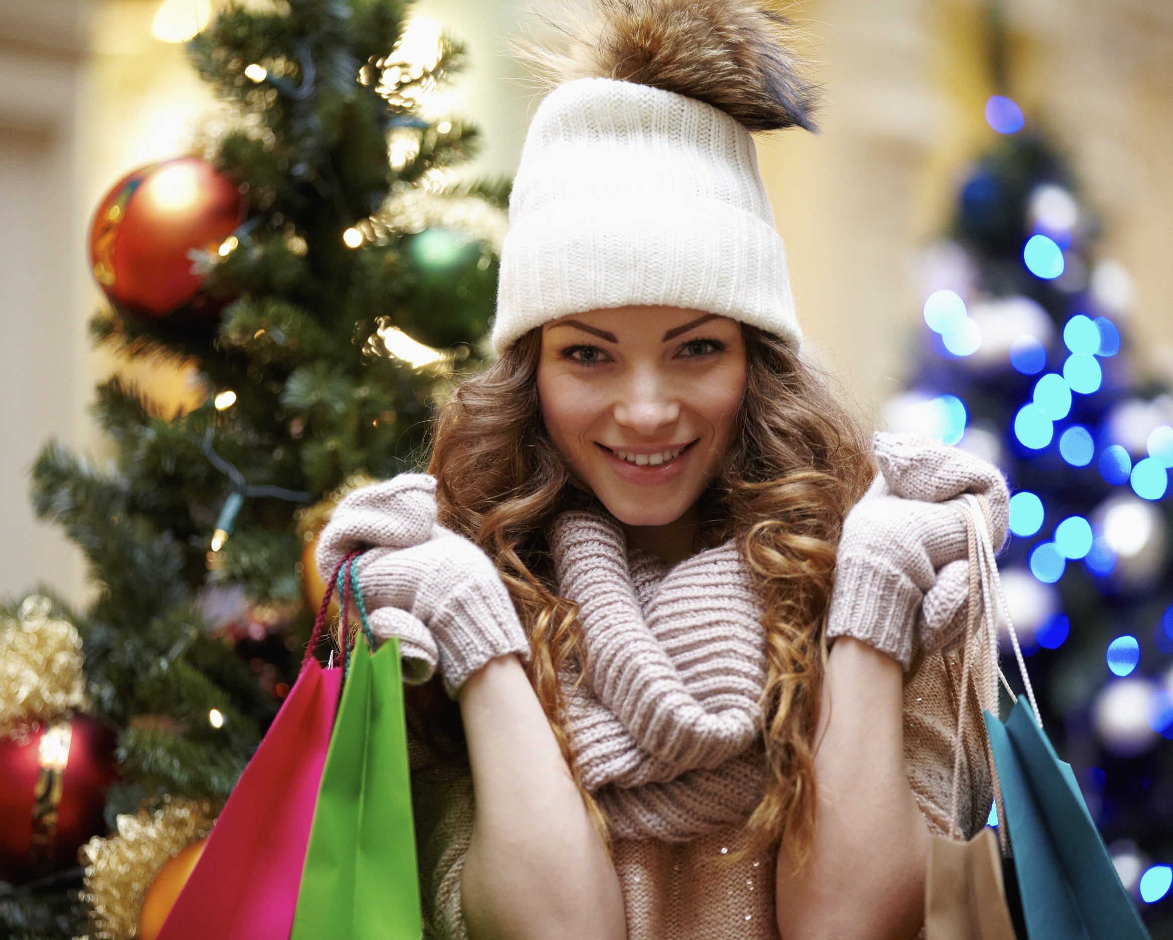 Young female with shopping bags and christmas tree