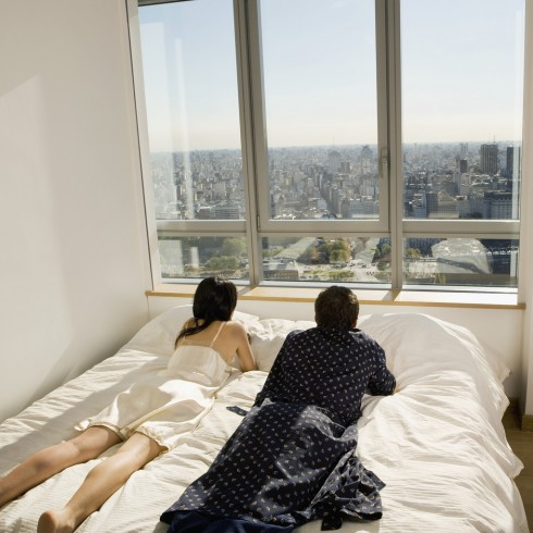 Hispanic couple laying on bed next to window