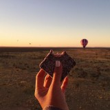 "A hot air balloon to watch the sun rise deep in Australia's outback, the Red Desert. Here she is eating a Lamington, a very Australian cake described as ""sponge cake covered in a dark rich chocolate coating and rolled in coconut shaving""."