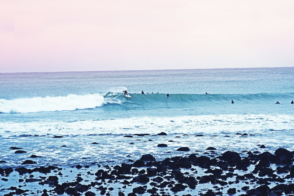 Surfers catching waves at Manu Bay